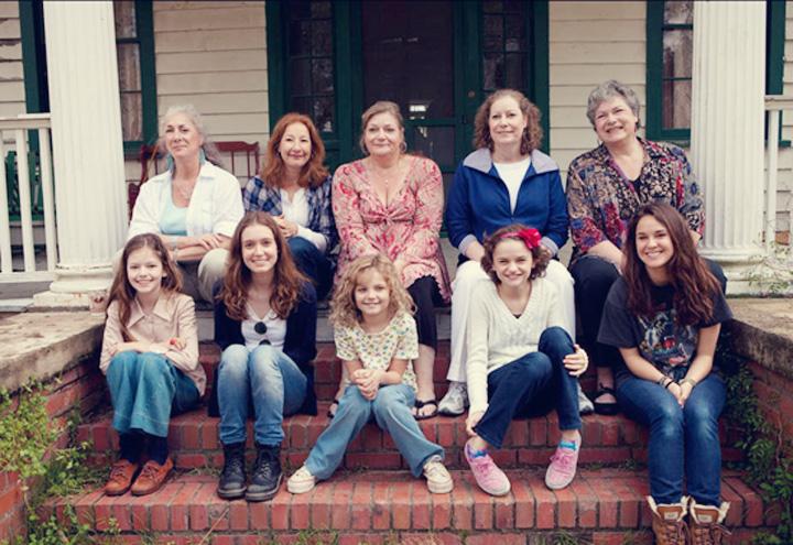 Na escada de baixo estão sentadas as atrizes que interpretaram as cinco filhas dos Perron, e na escada de cima, respectivamente estão sentadas as verdadeiras filhas que passaram pelo terror em Harrisville - Filme Invocação do Mal