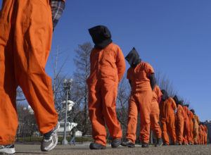 "Members of the group ""Witness Against Torture"" dressed in orange prison jumpsuits protest against the detention camp at Guantanamo Bay, along Pennsylvania Avenue in Washington D.C. January 10, 2012.  REUTERS/Larry Downing   (UNITED STATES - Tags: POLITICS CIVIL UNREST SOCIETY) - RTR2W40K"